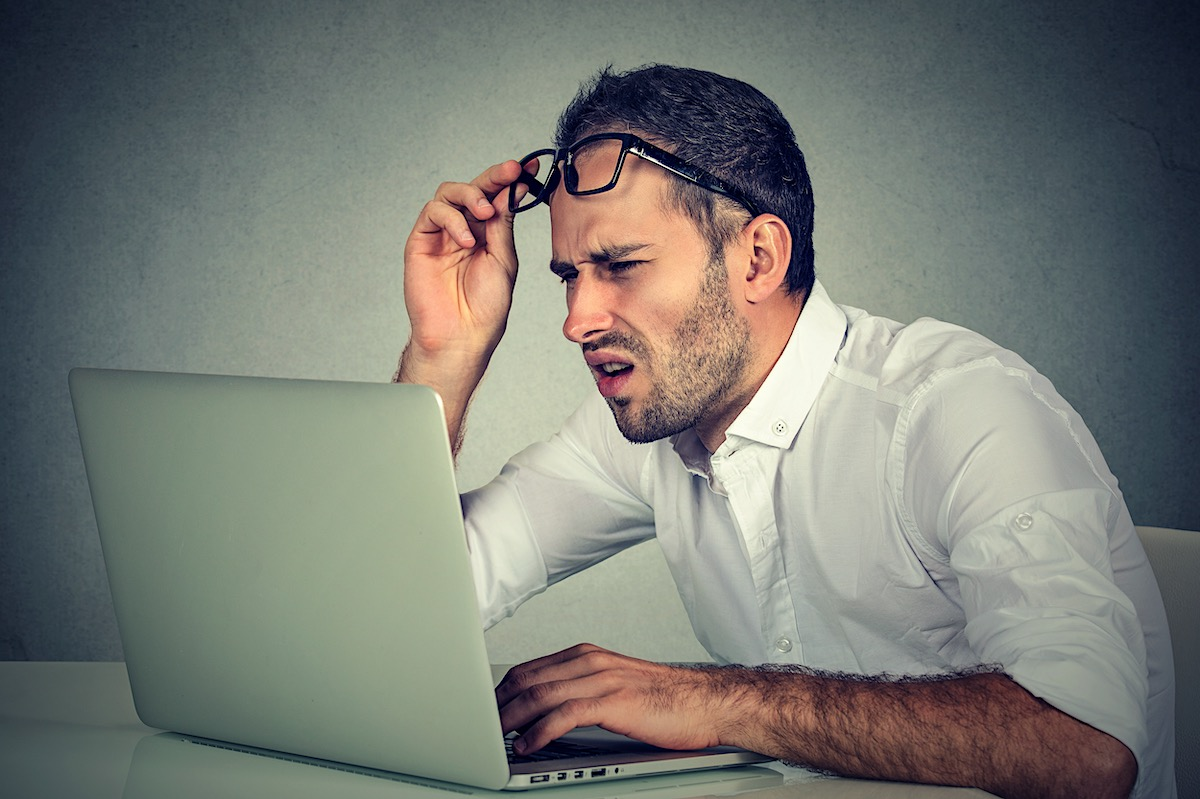 Puzzled and confused man looking at the laptop screen