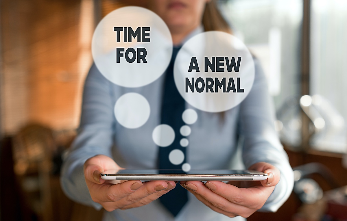 Woman holding an electronic tablet and saying it is time for a new normal